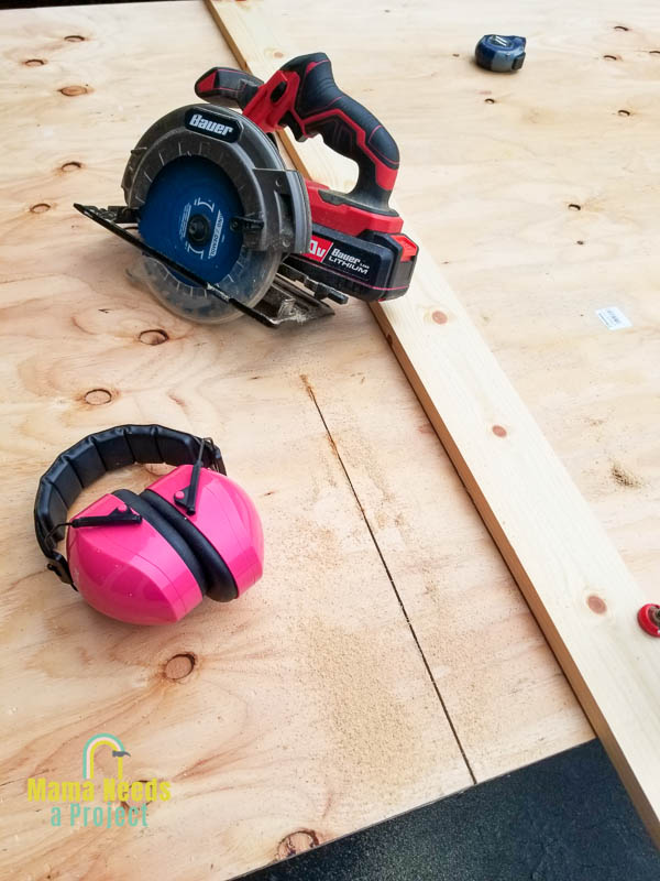 circular saw, ear protection and tape measure on a sheet of plywood