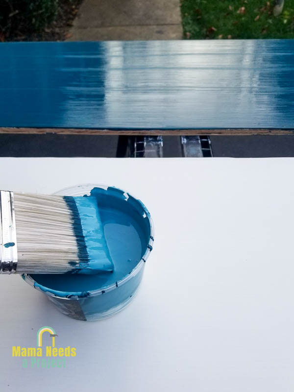 paint brush with blue paint on a sheet of plywood that has been painted with primer