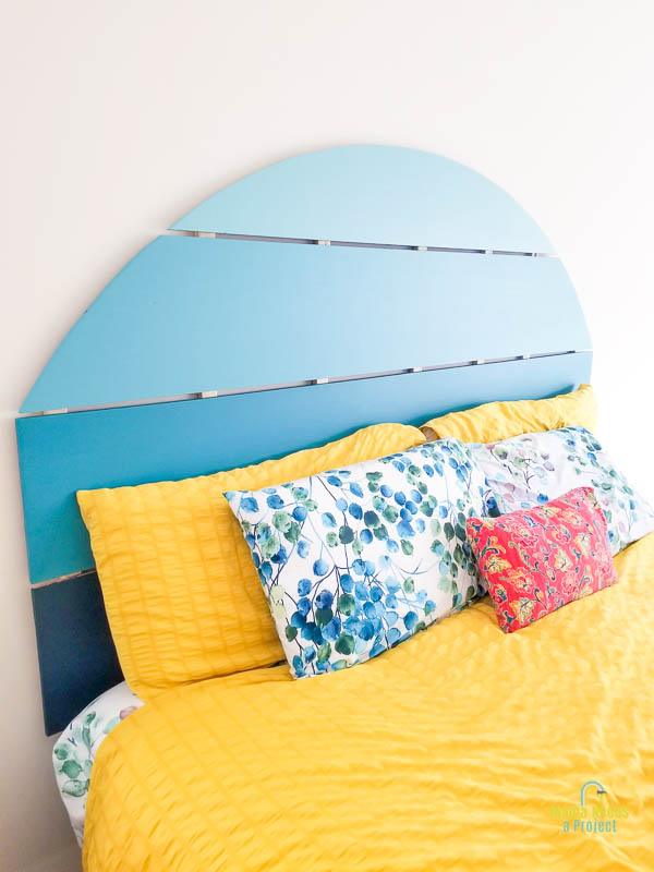 vertical image of half circle headboard painted in shades of blue and mounted to white wall with colorful bedding