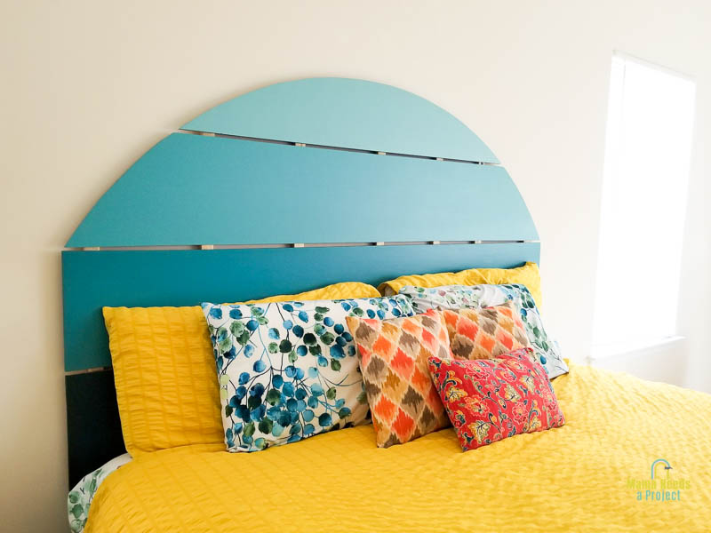 side view of a blue half circle shaped headboard and bed with yellow bedding and colorful pillows against a white wall