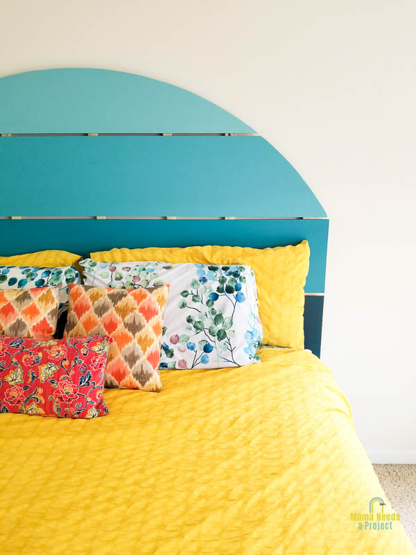 vertical image of half circle headboard painting in shades of blue and mounted to wall at the head of a bed