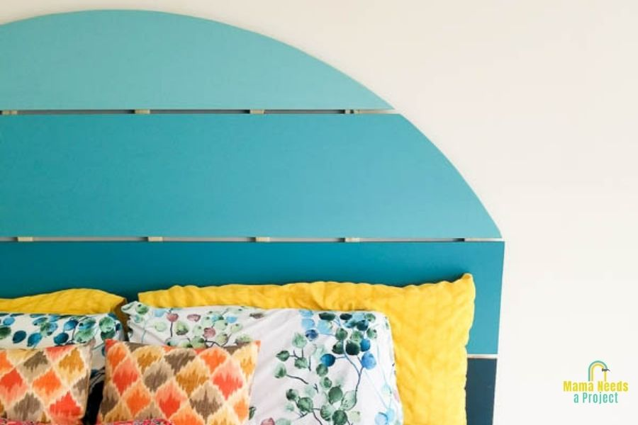 half circle shaped headboard in shades of blue with colorful bedding