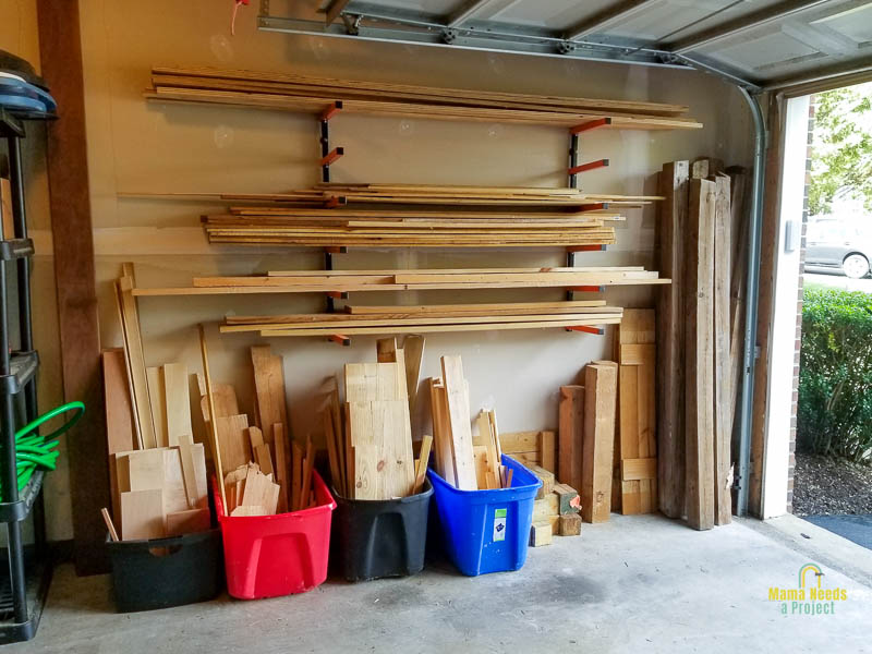 lumber rack on wall of garage with lumber on the rack and bins underneath, showing garage door and space around lumber rack
