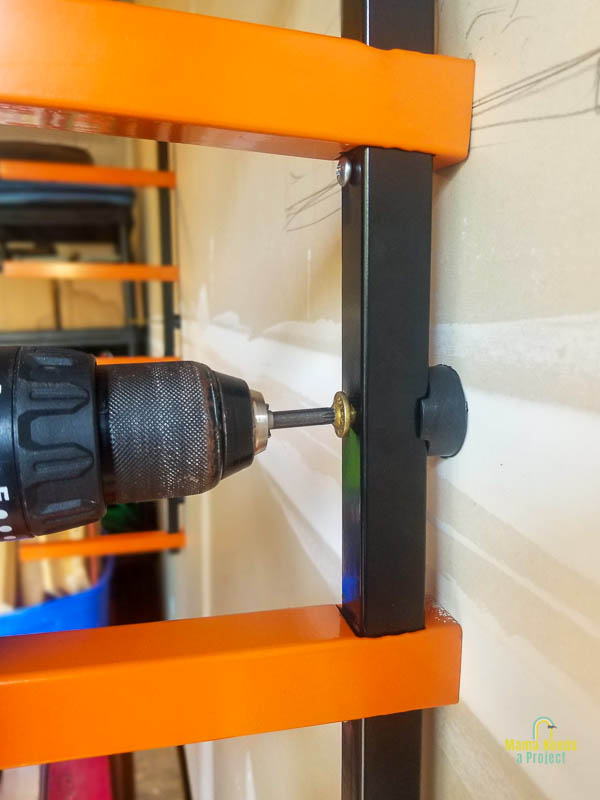 installing lumber rack to wall with a drill and spacers