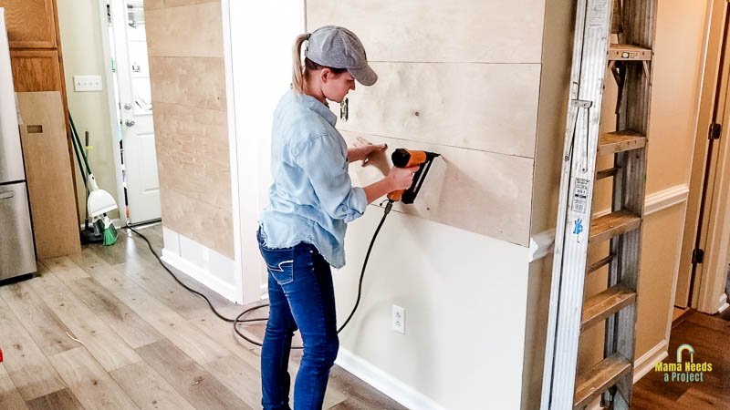Use a brad nailer to attach wood planks to the wall for DIY modern shiplap wall