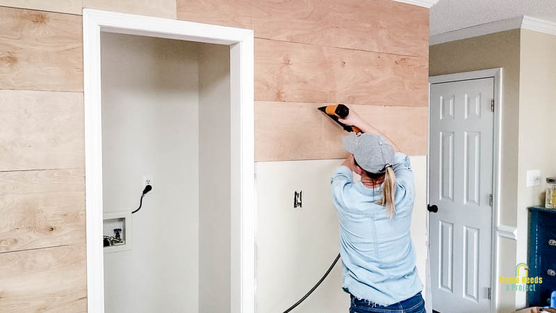 attach cut wood planks to wall with a brad nailer for DIY modern shiplap wall