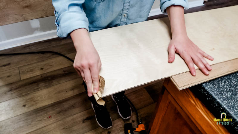 sand edges of DIY shiplap before attaching to wall with a sheet of sandpaper