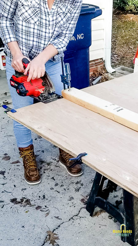 Using circular saw to cut sheets of underlayment; 2x4 clamped to underlayment as a saw guide