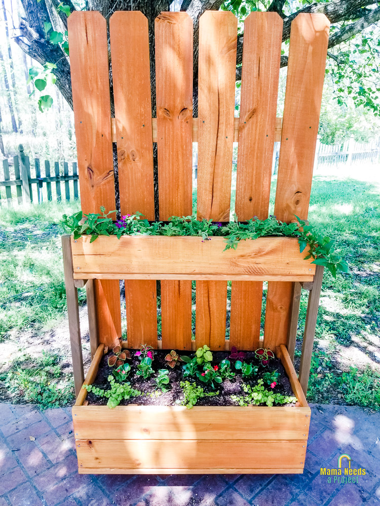 completed flower tower - two levels of flower boxes connected to a picket fence backer with flowers planted inside boxes