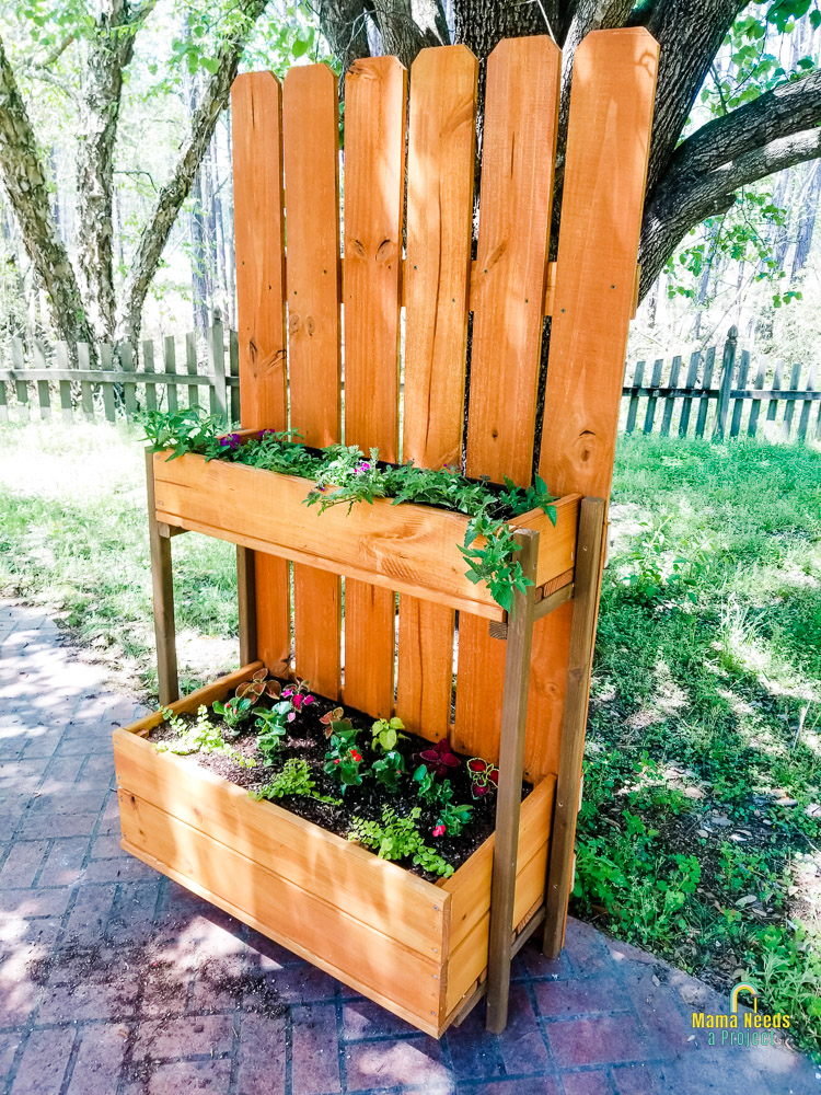 completed Picket Fence Flower Tower in front of a tree and green grass with flowers planted inside flower boxes