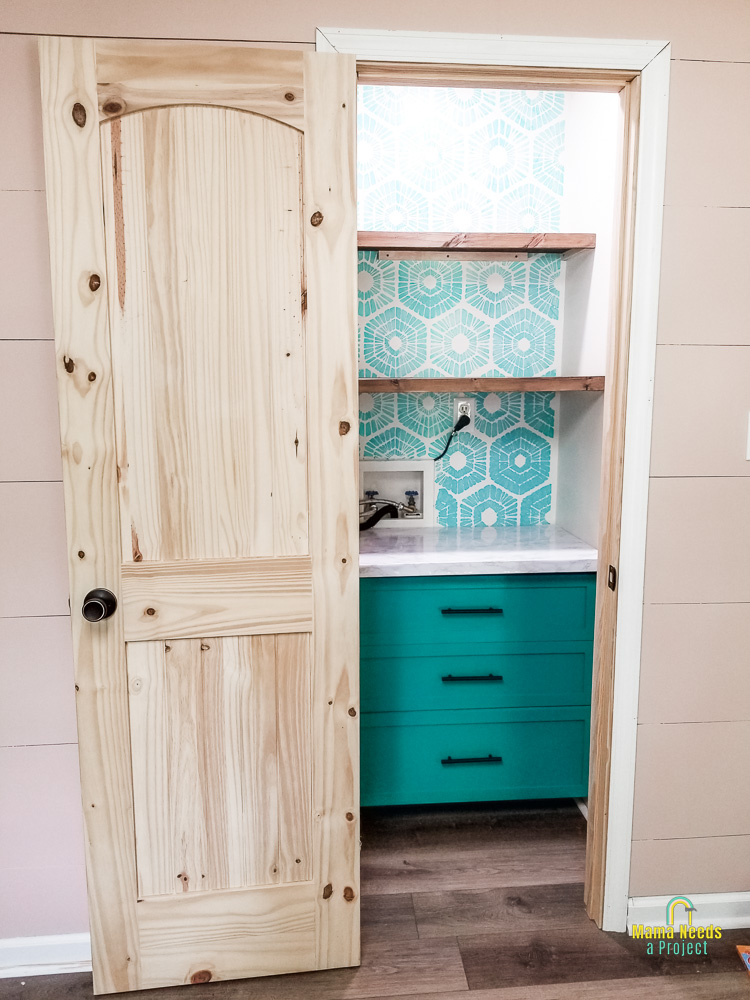 DIY small closet pantry with wood shelves, green drawers and a blue circle pattern on wall with a natural pine door opened