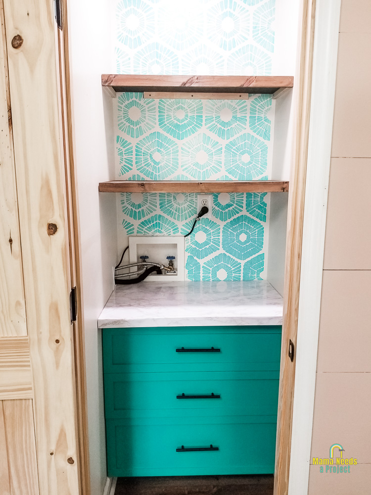 completed DIY pantry with wood shelves, green drawers, faux granite countertop and a blue stenciled wall