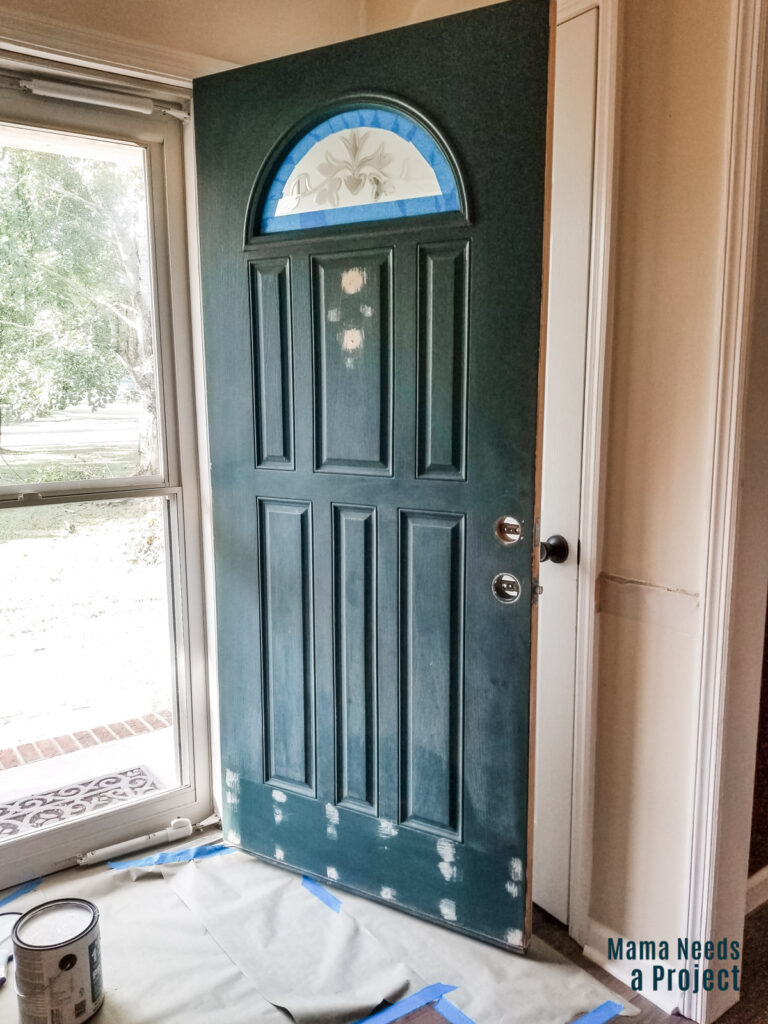 front door with hardware removed and holes filled with plastic wood to prepare for painting