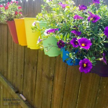 purple flowers in upcycled nursery pots fence art