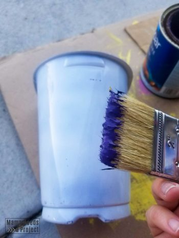 Painting plastic nursery pot purple after spraying with primer