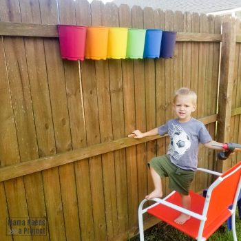 mounting upcycled plastic nursery pots to fence with a toddler
