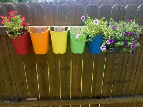 Upcycled plastic nursery pots mounted to fence with flower planted, rainbow colors